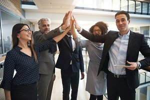 Business team giving high five in office
