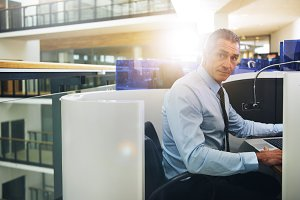 Confident businessman looking at camera while browsing laptop