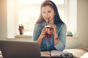 Female entrepreneur sitting with drinking jar at laptop