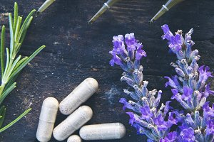 Natural medicine in ampules and pills on wooden background
