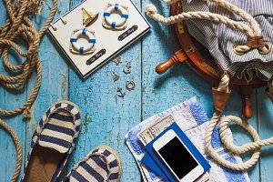 Striped slippers, phone and maritime decorations on the wooden background