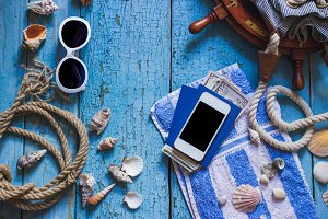 Striped towel, phone and maritime decorations on the wooden background
