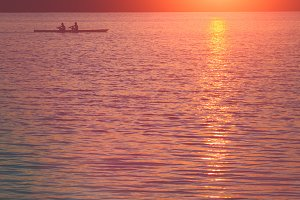 Team work of young men in a row boat silhouetted at sunset. Beautiful big sun light flares