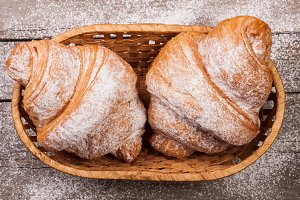 two croissants sprinkled with powdered sugar in a wicker basket on old wooden board Top view
