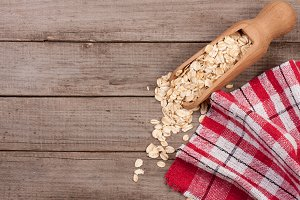 Oat flakes in a wooden scoop on old wooden background with copy space for your text. Top view