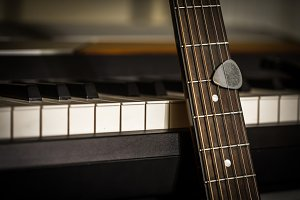 musical instruments piano keys and acoustic guitar with plectrum