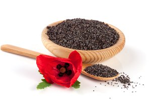 Poppy seeds in a wooden bowl and spoon with a flower