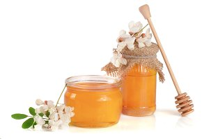 Jar of honey with flowers of acacia isolated on white background