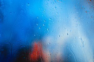 Drops on the glass rain blue background