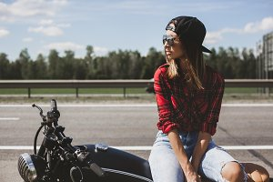 Biker girl sitting on motorcycle