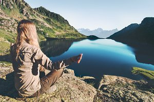 Woman meditating yoga at blue lake