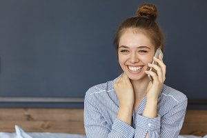 Beautiful young smiling female with bun wearing stripped shirt sitting at bedroom in morning communicating over mobile phone being happy to hear her boyfriend voice. Pretty girl having morning call