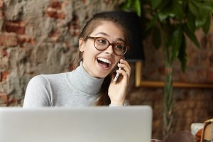 Cheerful excited young European female wearing grey turtle neck sweater and eyeglasses laughing with mouth wide opened as she receives good positive news during phone conversation with friend
