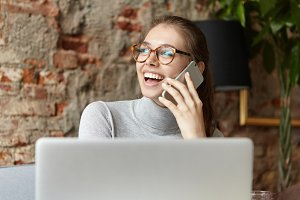Cute young Caucasian woman dressed casually sitting at restaurant with portable notebook pc on table and talking on cell phone, smiling, looking away with happy excited expression on her face