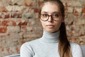 Close-up portrait of attractive woman with big green eyes, full lips, pure skin and fair-haired pony tail wearing big glasses and casual gray sweater isolated over brick wall. Woman resting at home