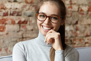 Happy young female with charming green eyes having her hair tied in pony tail wearing big glasses and sweater sitting at cozy sofa over brick wall holding hand under her chin having broad smile