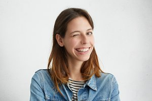 Indoor portrait of beautiful girl dressed in denim jacket over striped top smiling broadly and winking mysteriously at camera, having playful look. Positive human facial expressions and emotions