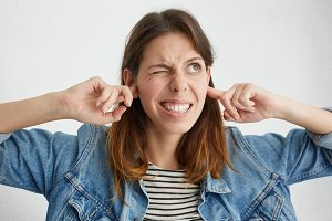 Stop making this annoying sound! Headshot of unhappy stressed out young female making wry face, plugging ears with fingers, irritated with loud noise coming from neighbours who live above her