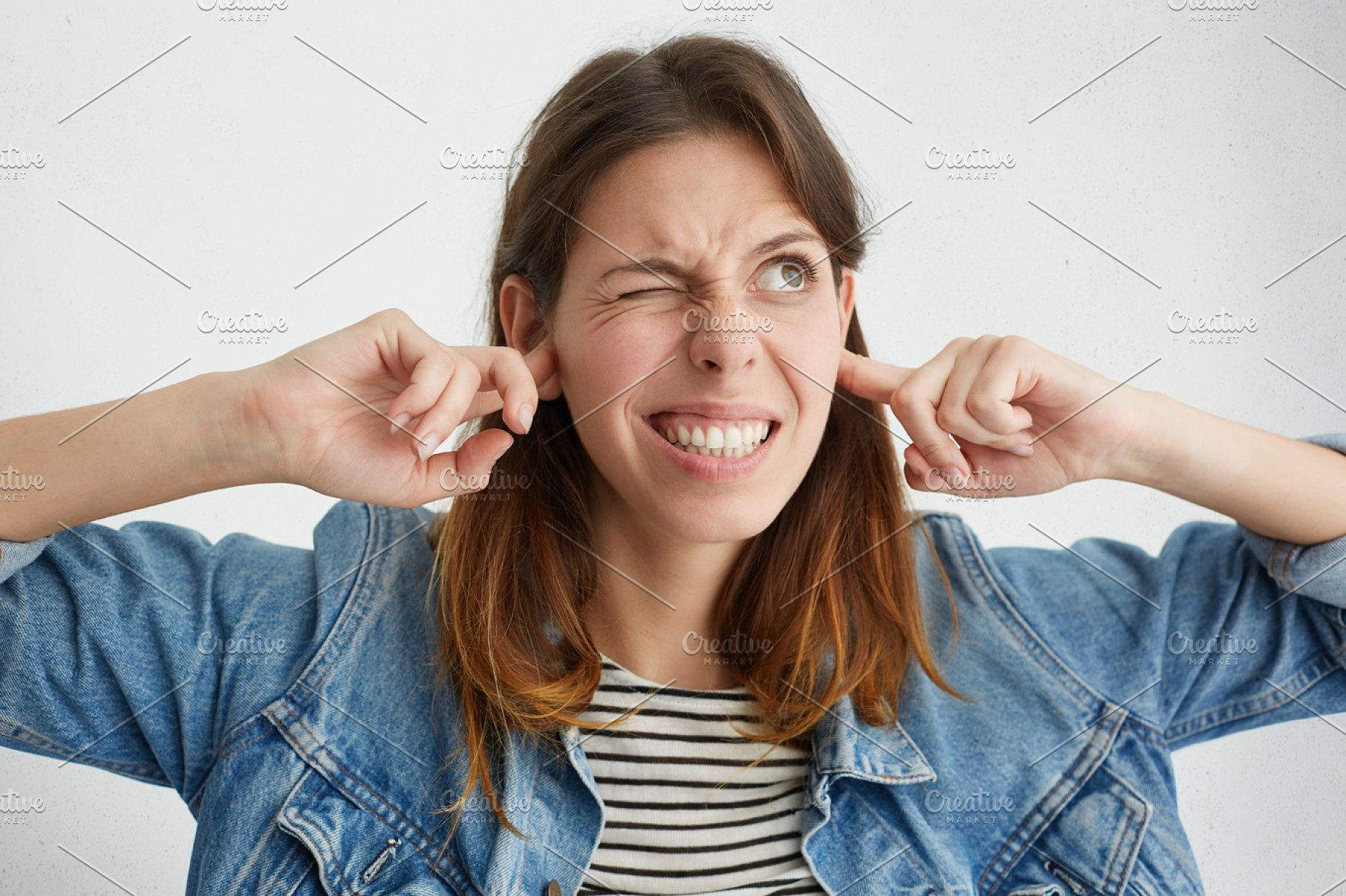 Stop making this annoying sound! Headshot of unhappy stressed out young  female making wry face, plugging ears with fingers, irritated with loud  noise