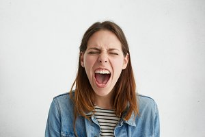 Studio shot of emotional stressed female dressed in trendy clothing shouting in fury and rage, closing eyes tight and opening mouth widely, having mad, furious or fed up look. Human emotions