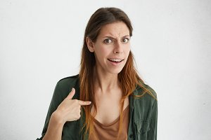 Portrait of beautiful confused woman pointing at herself with index finger. Offended female having quarrel looking with wonder pointing at herself proving her guiltlessness. Surprised angry woman