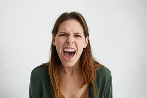 Close-up of irritated woman looking angrily in camera shouting having wide opened mouth being annoyed. Pretty woman wearing casual clothes having bad mood looking having rage and frowning expression