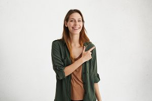 Horizontal studio shot of good-looking and cheerful young female wearing casual clothes keeping her index finger pointed at white blank wall with copy space for your text or advertising content
