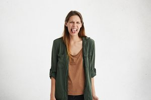 Negative human reaction, feelings and attitude. Portrait of disgusted squeamish teenage girl in casual wear grimacing, sticking out her tongue, feeling nauseous because of bad smell or stink