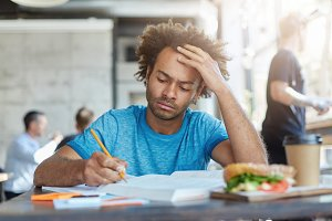 Concentrated casually dressed dark-skinned unshaven student studying at coffee shop, writing down in exercise book, making research or preparing for examination at college, having serious look