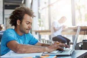 Stylish Afro American student keyboarding on laptop computer while sitting at cafe table with textbooks, working on homework, having focused concentrated look. People, modern technology and education
