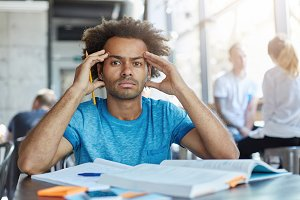 Handsome dark-skinned bearded student with Afro haircut squeezing temples, having headache while preapring for exams or tests night and day, looking at camera with painful frustrated expression