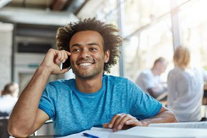 Attractive cheerful Afro American student in blue t-shirt smiling broadly while having nice conversation on mobile phone, sitting at coffee shop during lunch and waiting for his girlfriend to join him