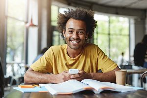 Funny dark-skinned man with African hairstyle working on course paper while sitting in cafe during lunch break holding smartphone being happy to finish his work. African guy with broad smile in cafe