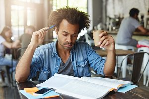 Concentrated thoughtful black European student with Afro hairstyle scratching head with pen, drinking hot tea at cafe, preparing for French lesson at college, translating article in textbook
