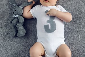 newborn to three months lying on the bed with the number three
