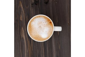 Top view of a white cup of cappuccino on a wooden black table.