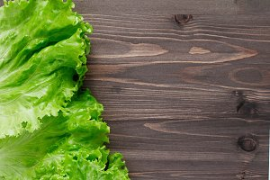 Top view of fresh lettuce leaves on wooden table. Copy space.