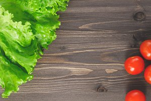 Top view of fresh lettuce leaves and cherry tomatoes on wooden table. Place for text.