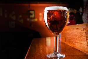 Glass of fresh beer on counter in pub