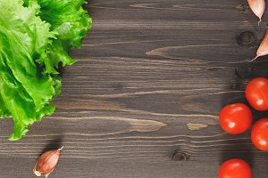 Top view of fresh lettuce leaves, garlic and cherry tomatoes on wooden table. Vegetable background.