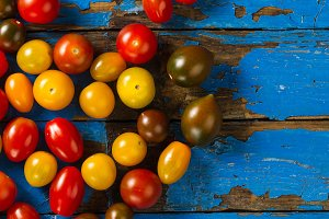 Tasty colorful tomatoes on blue