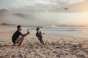 Father flying drone and son running