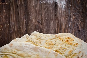 Homemade freshly baked Flatbread - Middle Eastern multi seeded flatbread with seasame seeds on woode3n background. Toned image
