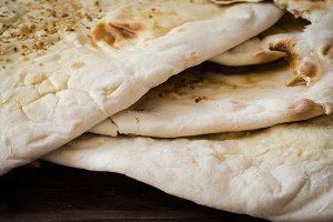 Closeup Homemade freshly baked Flatbread - Middle Eastern multi seeded flatbread with seasame seeds on woode3n background. Toned image