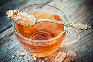 Tea cup and cane sugar i spoon.