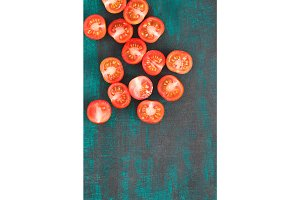 Cherry tomatoes on textured old blue and black wood background. Copy space.