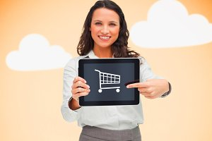 Businesswoman holding a tablet pc showing a shopping symbol against orange background with clouds