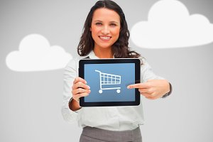 Woman standing while holding a digital tablet with shopping app on grey cloud background