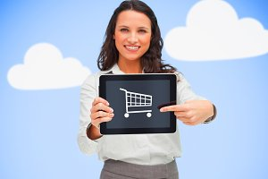 Businesswoman holding a tablet pc while smiling showing trolley symbol against blue background with clouds