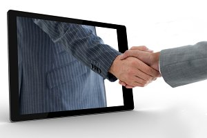 Businessman reaching out from tablet and shaking hands